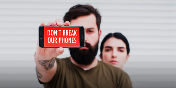 "Man holding a phone that displays the image ""Don't Break Our Phones"", woman standing behind him"